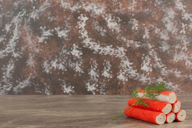 Smakelijke krabstokken op marmeren achtergrond.