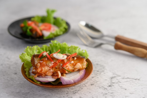Smakelijke kruidige ingeblikte sardinesalade met kruidige saus in houten kom