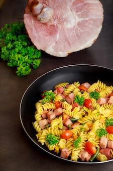 Smakelijke macaroni met groenten en gesneden varkensham.