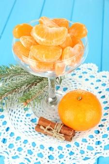 Smakelijke mandarijnenplakken in glazen kom op blauwe ondergrond