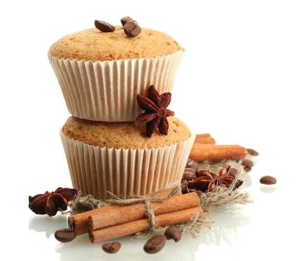 Smakelijke muffincakes op geïsoleerde jutekruiden en koffiezaden