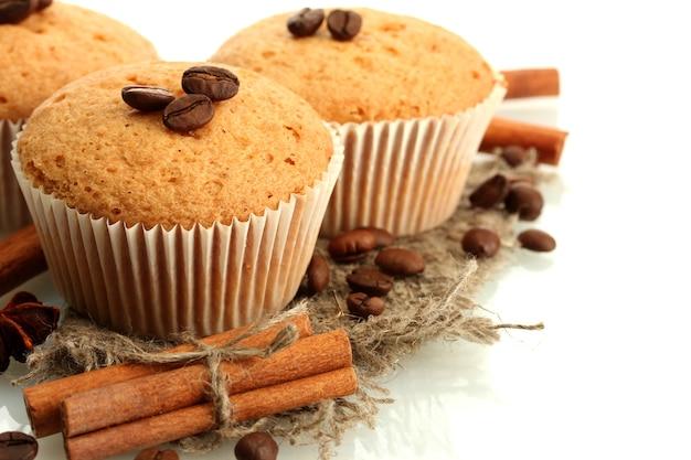 Smakelijke muffincakes op jute, kruiden en koffiezaden, die op wit worden geïsoleerd