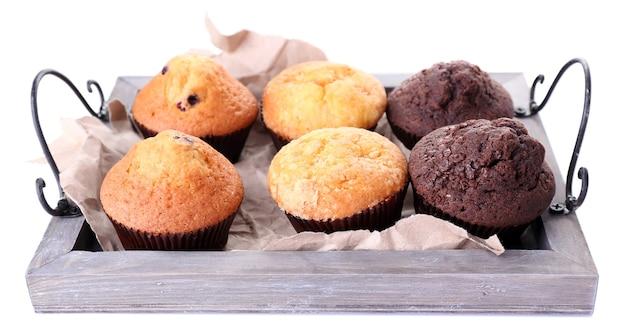Smakelijke muffins op houten dienblad op wit