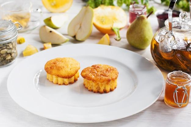 Smakelijke muffins op witte plaat, peer en thee