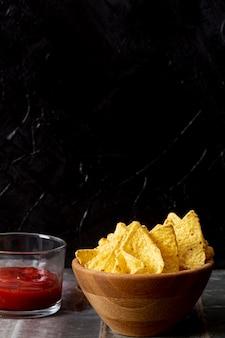 Smakelijke nacho's in houten kom en saus