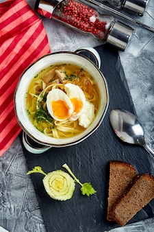 Smakelijke noedels in een kippenbouillon met gekookt ei