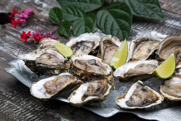 Smakelijke oesters op ijs met citroen op houten oppervlak