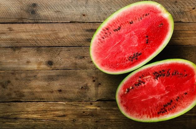 Smakelijke organische watermeloen die in de helft op houten wordt gesneden