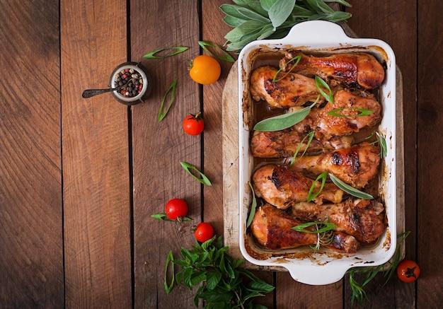 Smakelijke oven gebakken gouden kip drumsticks in een ovenschaal tafel. bovenaanzicht