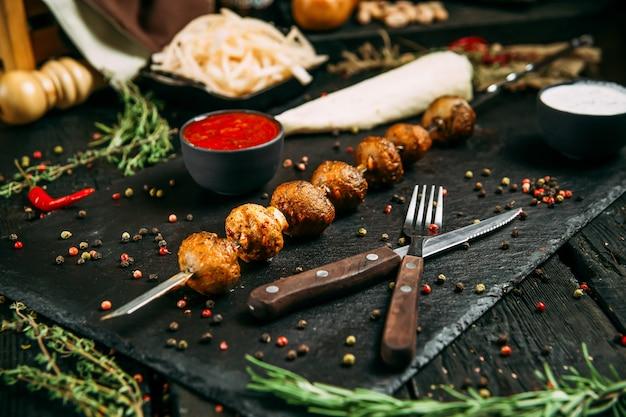 Smakelijke paddenstoelen kebab shashlyk spiesjes met rode saus en gepekelde ui op een zwart bord op een donkere houten achtergrond