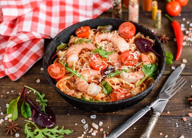 Smakelijke pasta met garnalen en tomaat op een koekenpan