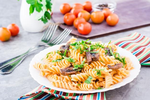 Smakelijke pasta met gebakken champignons en verse kruiden op een bord, cherry tomaten en peterselie in een glas op een tafel