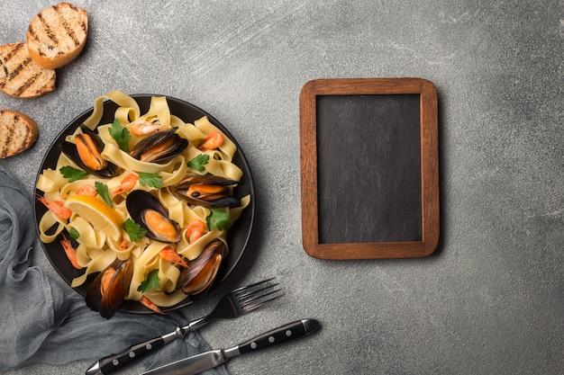 Smakelijke pasta met mosselen, inktvis, peterselie en citroen, bovenaanzicht.