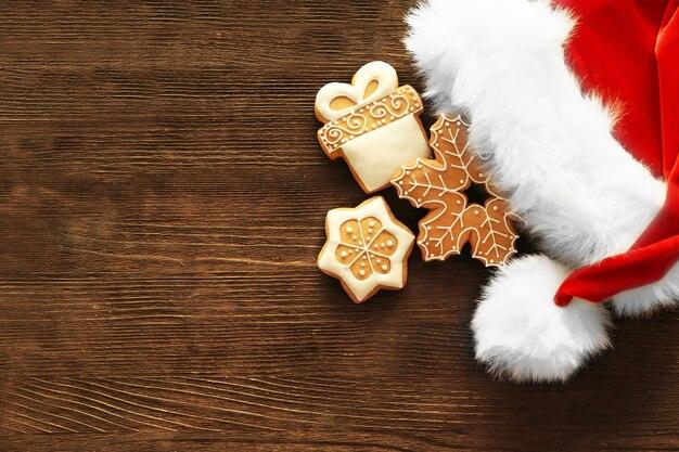 Smakelijke peperkoekkoekjes en kerstmanhoed op houten achtergrond