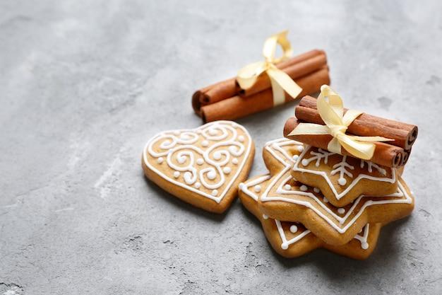 Smakelijke peperkoekkoekjes en pijpjes kaneel op geweven achtergrond