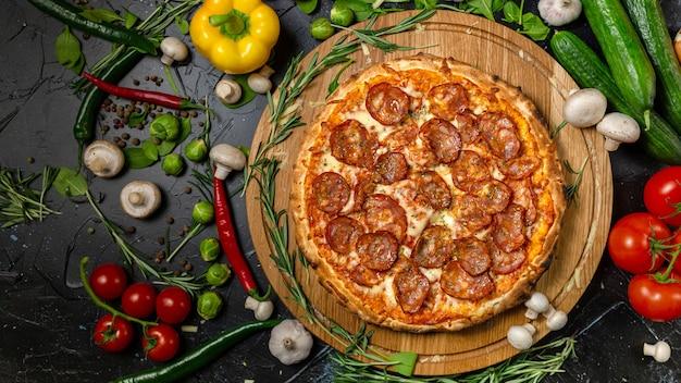 Smakelijke pepperoni pizza en koken ingrediënten tomaten basilicum op zwarte betonnen achtergrond. bovenaanzicht van hete pepperoni pizza. met kopie ruimte voor tekst. plat leggen. banner