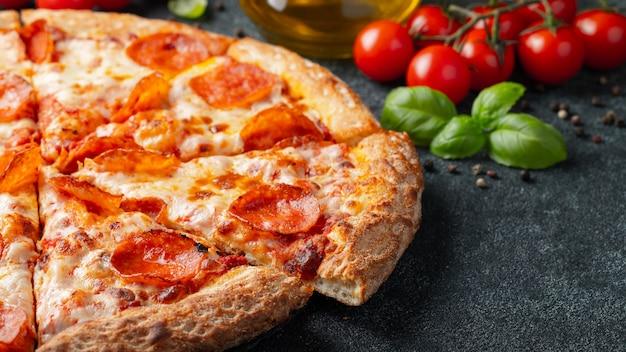Smakelijke pepperonispizza en het koken het basilicum van ingrediëntentomaten op zwarte concrete achtergrond