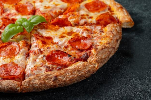Smakelijke pepperonispizza op een zwarte concrete achtergrond.