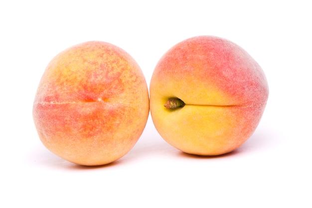 Smakelijke perziken op wit