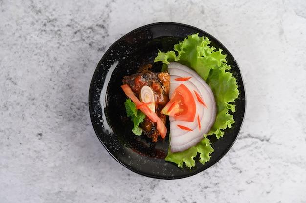 Smakelijke pittige ingeblikte sardinesalade in pittige saus in zwarte keramische kom
