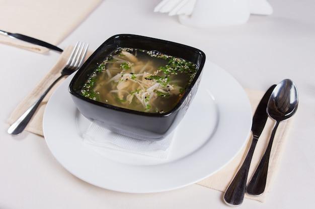 Smakelijke pittige soep op zwarte kom geserveerd op witte ronde plaat met gebruiksvoorwerpen aan zijkanten.