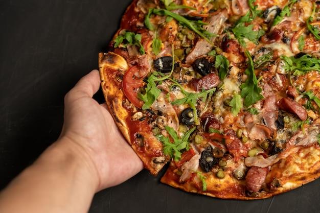 Smakelijke pizza met gerookte worsten bacon kaas tomaat rucola op zwart donker. met copyspace
