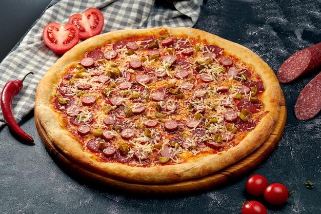Smakelijke pizza met hete jalapeno pepers, salami, worstjes, rode saus en parmezaanse kaas. donker oppervlak. italiaanse keuken