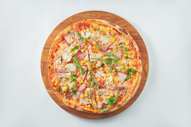 Smakelijke pizza met rode saus, ham, gerookte kip, maïs op een houten dienblad. witte achtergrond. italiaanse keuken