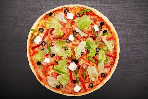 Smakelijke pizza met verschillende gearomatiseerde ingrediënten op donker