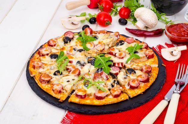 Smakelijke pizza salami, champignons en olijven op houten tafel