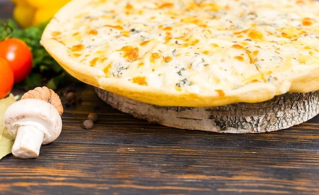Smakelijke pizza vier kazen op houten standaard