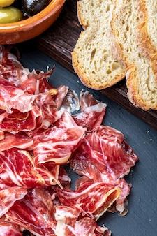 Smakelijke plakjes iberische ham op de voorgrond. olijfolie, brood, verse tomaat, olijven.