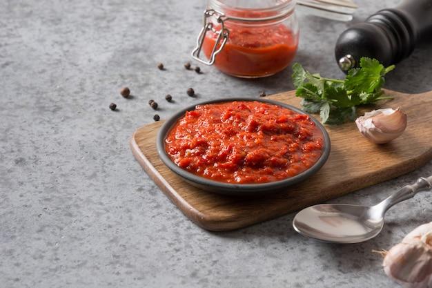 Smakelijke plantaardige ajvar van gebakken rode paprika op grijs. balkan-keuken. ruimte voor tekst.
