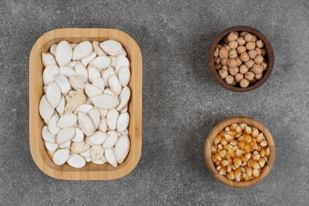 Smakelijke pompoenpitten, maïskorrels en erwten op marmer.