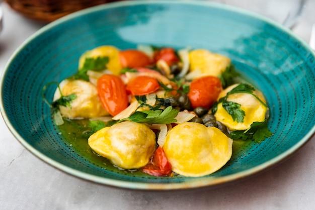 Smakelijke ravioli pasta in groene keramische plaat