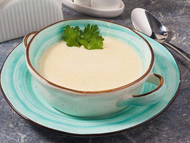 Smakelijke roomkaas soep in een blauw bord op een grijze achtergrond