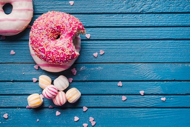 Smakelijke roze geglazuurde cakes en kleurrijk suikergoed