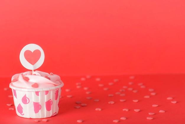 Smakelijke roze pastelkleur boterroom cupcakes op rode achtergrond
