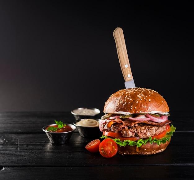 Smakelijke rundvleesburger met mes klaar om te worden geserveerd