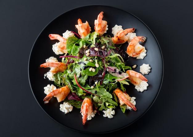 Smakelijke salade met tijgergarnalen, sla, salade en philadelphia-kaas op zwarte plaat.