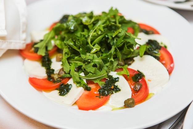 Smakelijke salade van tomaten, kaas en rucola op witte plaat in het restaurant