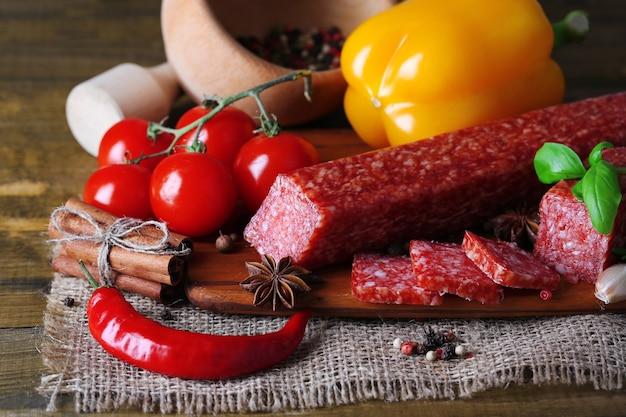 Smakelijke salamiworst en kruiden op houten