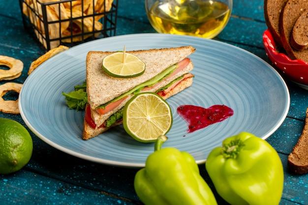 Smakelijke sandwich in blauw bord samen met groene paprika en olie op blauw