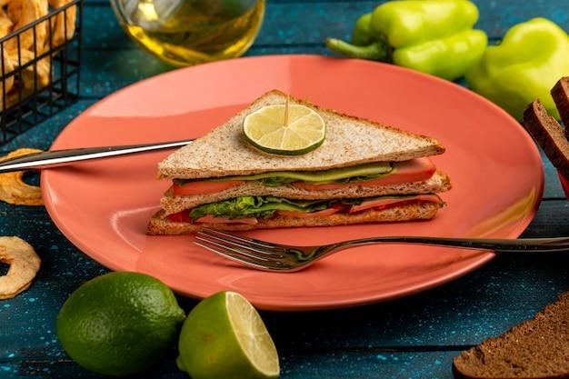 Smakelijke sandwich samen met groene paprika-olie en citroen op blauw