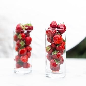 Smakelijke sappige aardbeien in een glas op een witte achtergrond