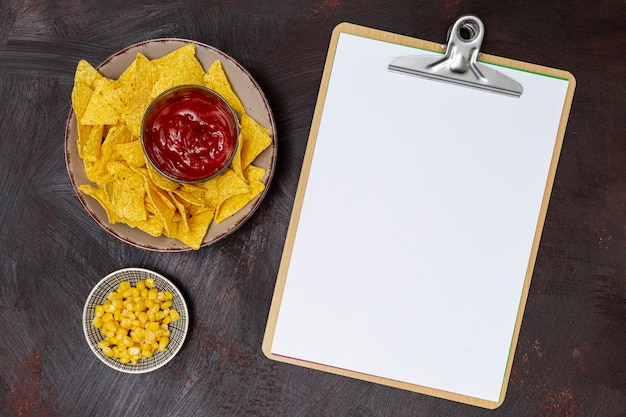 Smakelijke saus met nachos klembord en maïs