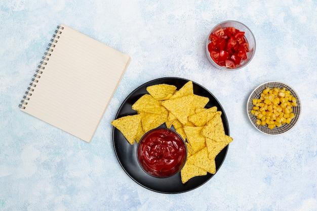 Smakelijke saus met nachosnotitieboekje en groenten