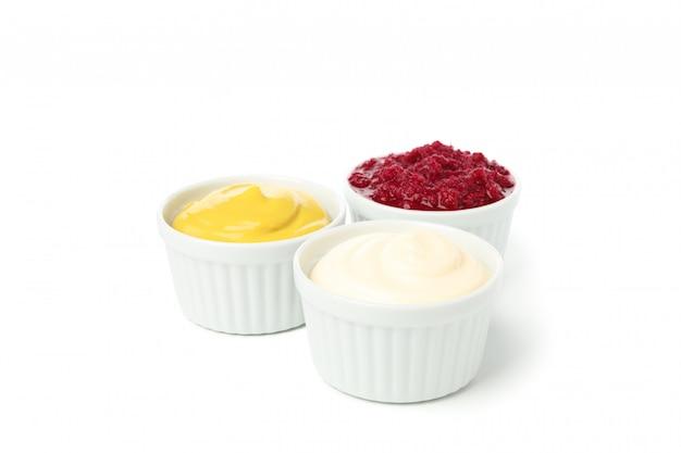 Smakelijke sauzen in kommen die op witte achtergrond worden geïsoleerd