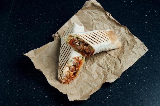 Smakelijke shoarma roll met vlees, salade en zelfgemaakte saus in dun pitabroodje op ambachtelijke papier op een zwarte tafel ... oosterse keuken. gesneden kebab met gegrild vlees.