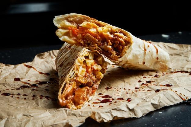 Smakelijke shoarmarol met vlees, salade en huisgemaakte saus in dun pitabroodje op ambachtelijk papier op een zwarte ondergrond. oosterse keuken. gesneden kebab met gegrild vlees.